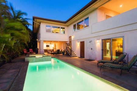 プールとホットタブ日没時の高級住宅 写真素材