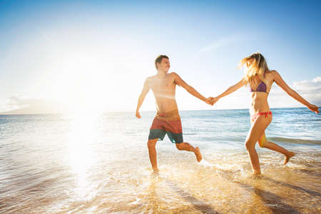 Happy couple running on a tropical beach in the ocean at sunset photo