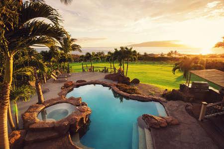 豪華な日没でプールを持つ家