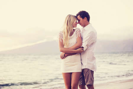 Romantic couple in love on the beach at sunset Imagens
