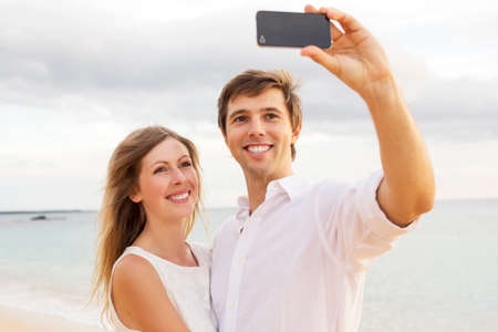 Happy young couple taking a selfie on the beach at sunset photo