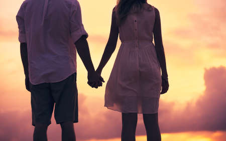 girls holding hands: Romantic couple in love holding hands on the beach sunset Stock Photo