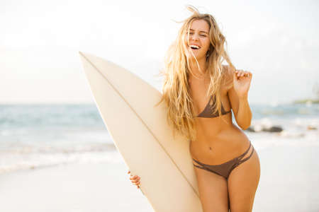 Beautiful carefree happy surfer girl on the beach at sunset. Beach culture lifestyle concept. photo