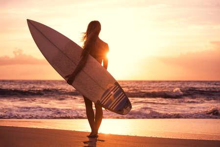 Silhouet van mooie surfer meisje op het strand bij zonsondergang