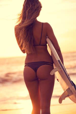 Silhouette de la belle fille de surfer sur la plage au coucher du soleil Banque d'images