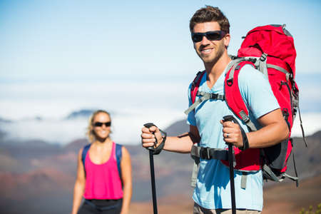 Man and woman hiking on beautiful mountain trail. Trekking and backpacking in the mountains. Healthy lifestyle outdoor adventure concept. photo