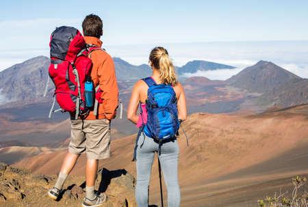 男と女の美しい山道をハイキングします。トレッキングやバックパックを背負って山の中。健康的なライフ スタイルの屋外の冒険のコンセプトです