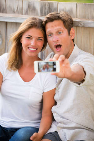 Happy young couple taking a selfie with smart phone
