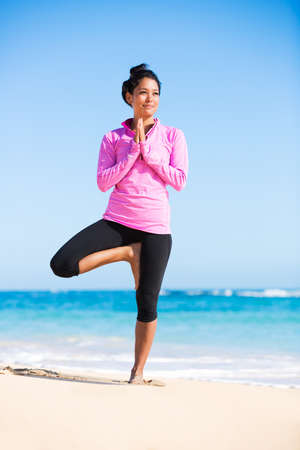 Happy relaxed young woman practicing yoga outdoors at the beach. Healthy natural lifestyle. photo