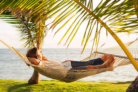 Romantic couple relaxing in tropical hammock at sunset photo