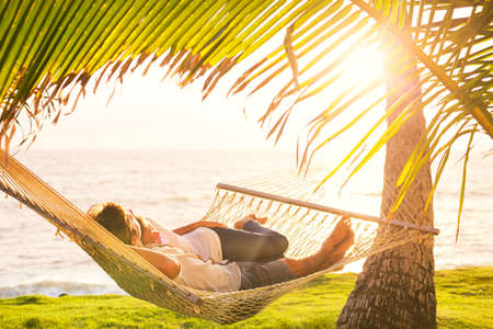 Romantic couple relaxing in tropical hammock at sunset Stock Photo