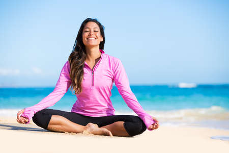 rest in peace: Happy relaxed young woman practicing yoga outdoors at the beach. Healthy natural lifestyle. Stock Photo