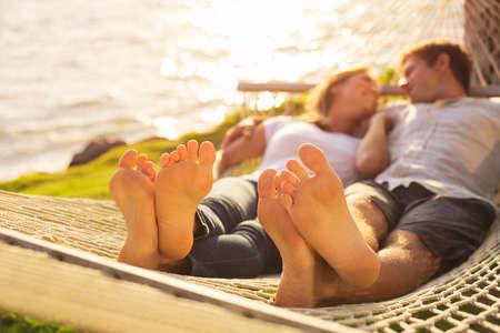 Pareja romántica de relax en hamaca tropical al atardecer, poca profundidad de campo, se centran en los pies.