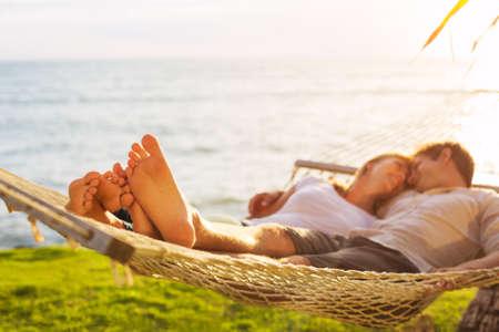 フィールドの日没、浅い深さで熱帯のハンモックでリラックスしたロマンチックなカップルの足に焦点を当てます。