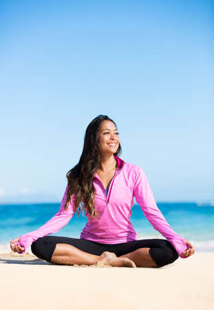 Beautiful young woman in yoga pose at the beach. Morning zen mediation outdoors. Practicing yoga. Healthy lifestyle. photo