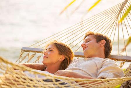 일몰 열대 그물 침대에서 휴식 로맨틱 커플