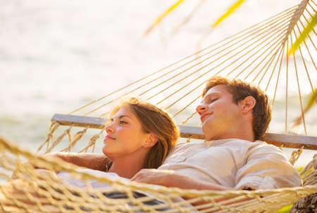 hammock: Romantic couple relaxing in tropical hammock at sunset Stock Photo