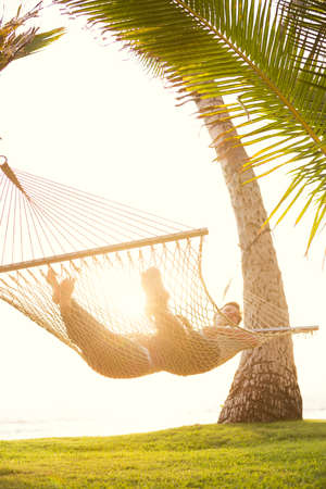 Romantic couple relaxing in tropical hammock at sunset Banco de Imagens