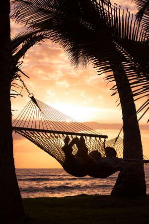 日没時の熱帯のハンモックでリラックスしたロマンチックなカップルのシルエット 写真素材