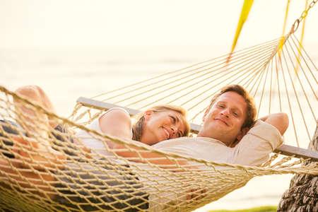 relaxamento: Par romântico relaxante em rede tropical ao pôr do sol