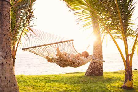 Romantische paar ontspannen in tropische hangmat bij zonsondergang