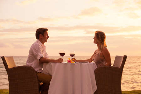 drink me: Couple sharing romantic sunset dinner on the beach Stock Photo