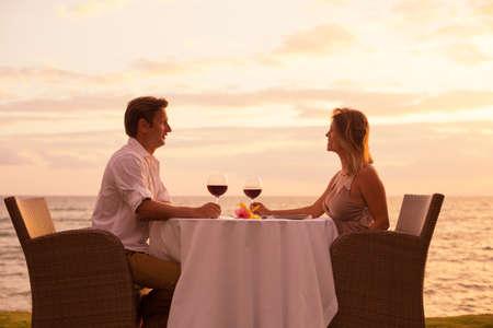 blissful: Couple sharing romantic sunset dinner on the beach Stock Photo