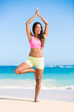 thai yoga: Happy relaxed young woman practicing yoga outdoors at the beach. Healthy active lifestyle. Zen Meditation.
