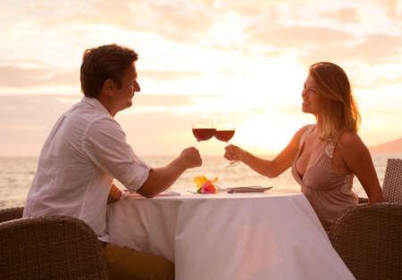 ビーチでロマンチックな夕日ディナーを共有するカップル