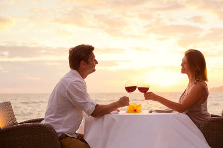 holiday dinner: Couple sharing romantic sunset dinner on the beach Stock Photo