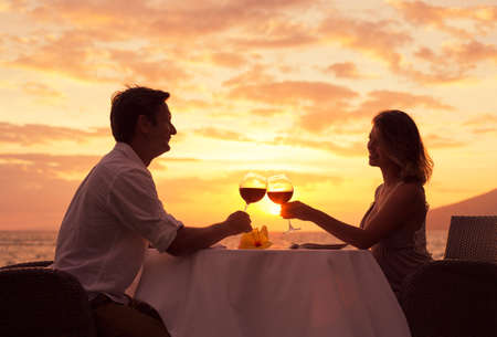 dinner table: Couple sharing romantic sunset dinner on the beach Stock Photo