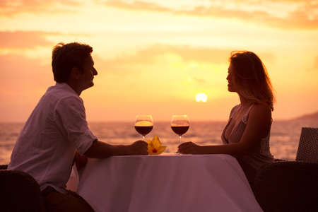 romantic dinner: Couple sharing romantic sunset dinner on the beach Stock Photo