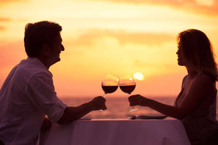 Couple sharing romantic sunset dinner on the beach Imagens