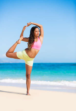 Happy relaxed young woman practicing yoga outdoors at the beach. Healthy active lifestyle. Zen Meditation. photo