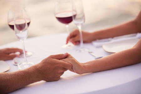Romantic couple holding hands at sunset dinner on the beach photo