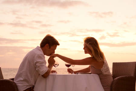 propose: Couple sharing romantic sunset dinner on the beach Stock Photo