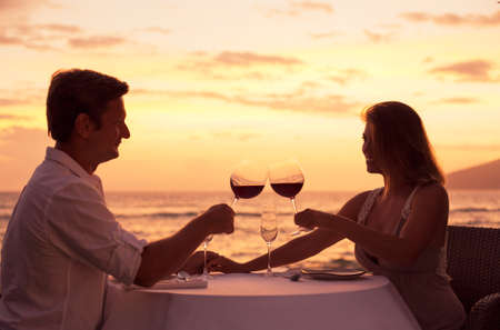Paar delen romantisch diner bij zonsondergang op het strand