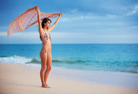 Beautiful Young Woman With Scarf on the Beach at Sunset. Travel and Vacation Concept. Fashion Lifestyle. photo