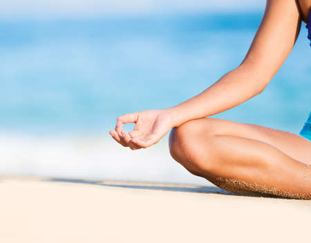 thai yoga: Happy relaxed young woman practicing yoga outdoors at the beach. Lotus position, Cloe up detail photo of hand. Stock Photo