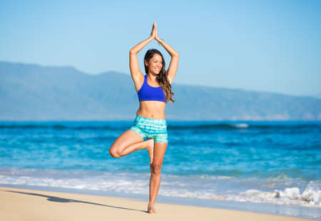 taichi: Happy relaxed young woman practicing yoga outdoors at the beach. Healthy active lifestyle. Zen Meditation.