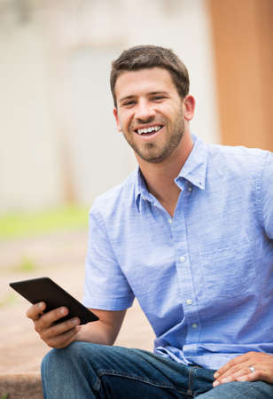 Young man reading E-book outside on steps photo