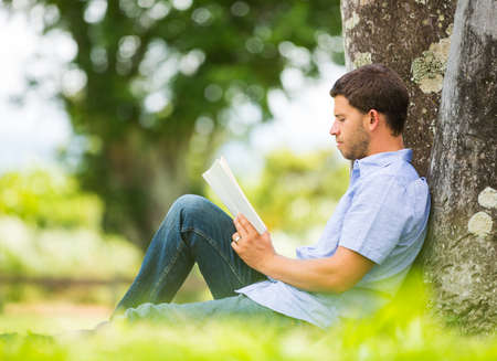 Man reading book in park, sitting under a tree. Relaxing outdoors reading. photo