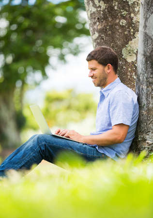 laptop outside: Young man working outside on laptop in park under a tree Stock Photo