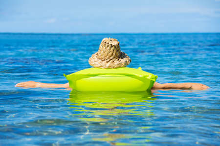 raft: Beautiful woman floating on raft in tropical ocean Stock Photo