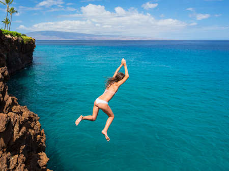 Woman jumping off cliff into the ocean. Summer fun lifestyle. photo