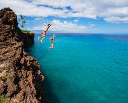 gente saltando: Diversi�n de verano, Amigos acantilado saltando en el oc�ano.