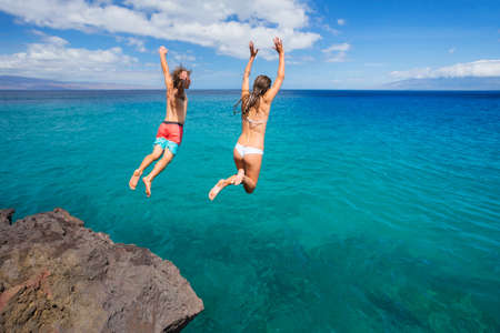 Summer fun, Friends cliff jumping into the ocean. Stock Photo - 30193395