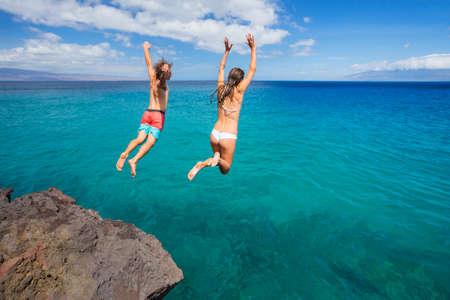 risky: Summer fun, Friends cliff jumping into the ocean.