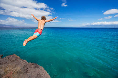 Man jumping off cliff into the ocean. Summer fun lifestyle. Imagens