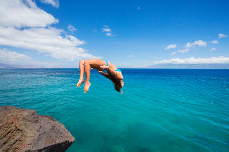 backflip: Woman doing backflip off cliff into the ocean. Summer fun lifestyle.